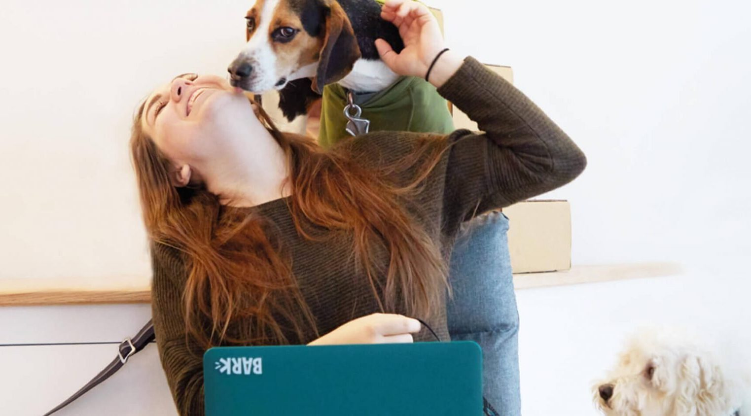 image of a dog mom getting kisses from her dog after giving her dog a Bark Box.