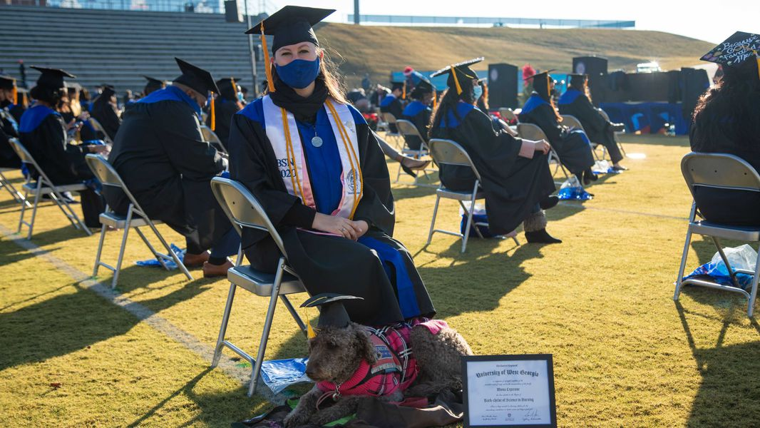 College student and dog smiling with their college degrees